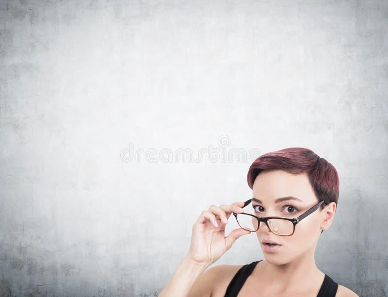 Zdziwiona kobieta bierze daleko szkła, beton obraz stock