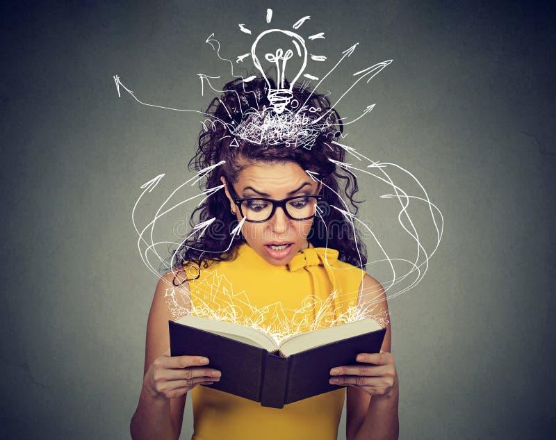 Zdziwiona kobieta czyta książkę zniewalającą niespodziewanym fabuła skrętem zdjęcia royalty free