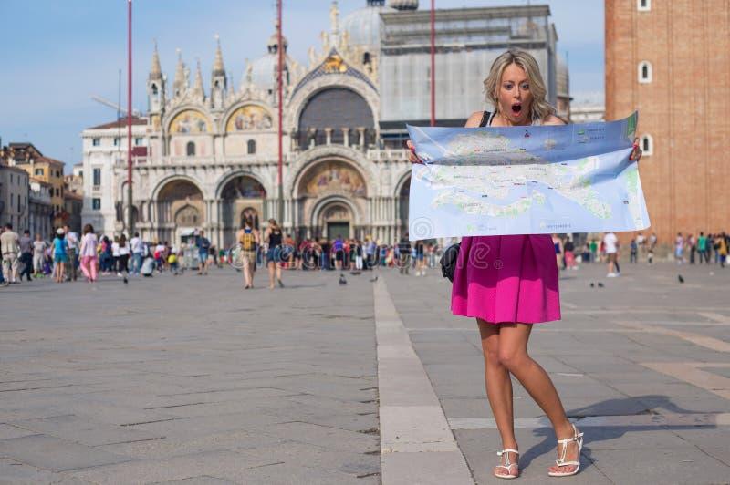 Zdziwiona kobieta patrzeje mapę obraz stock