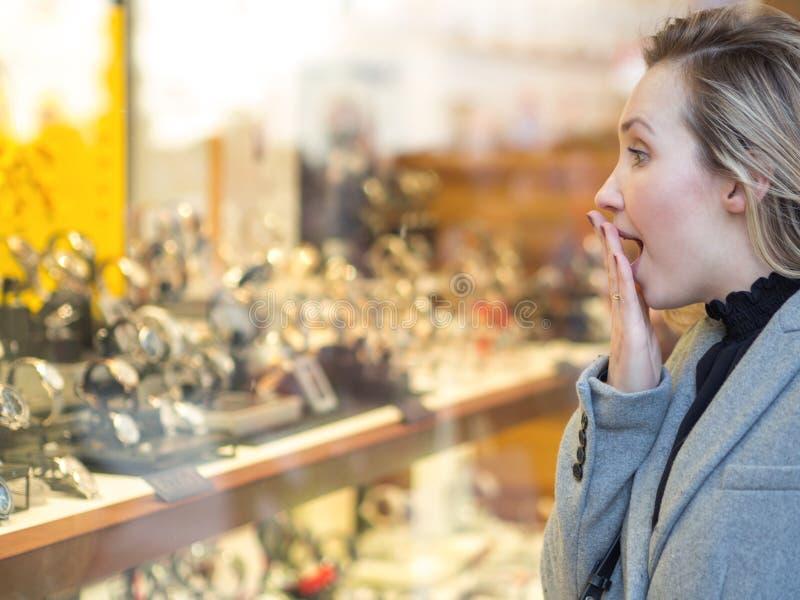 Zdziwiona kobieta patrzeje sklepowego okno obraz royalty free