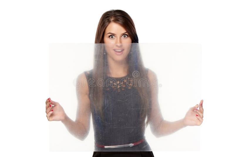 Zdziwiona kobieta trzyma przejrzystego prześcieradło klingeryt obrazy stock