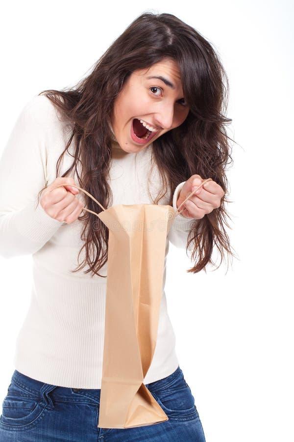 Zdziwiona kobieta trzyma torba na zakupy i patrzeje inside zdjęcia royalty free