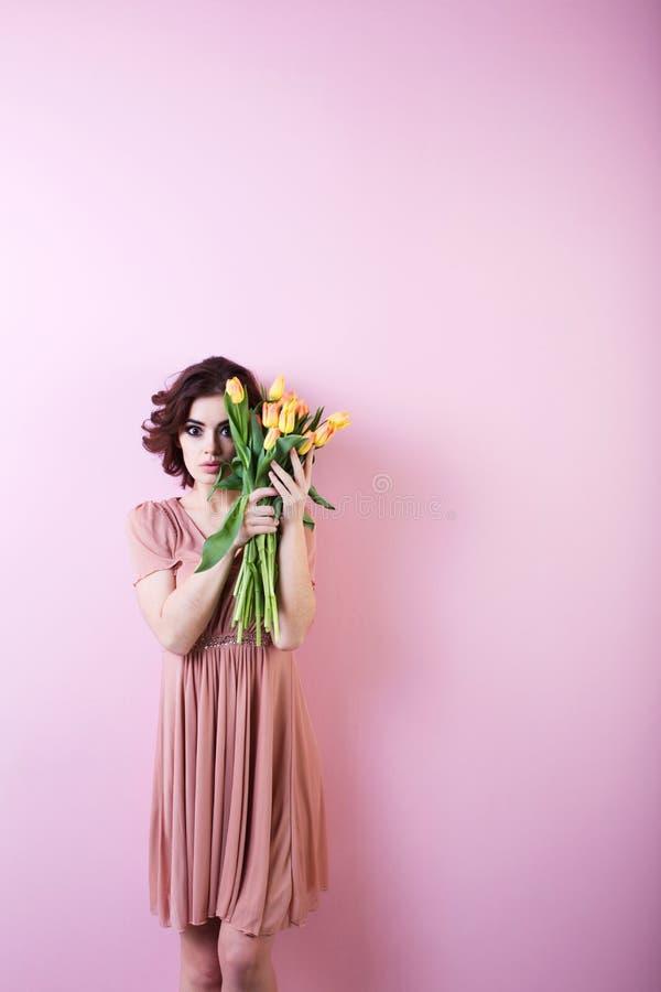Zdziwiona kobieta z bukietem kwiaty nad menchiami zdjęcie royalty free