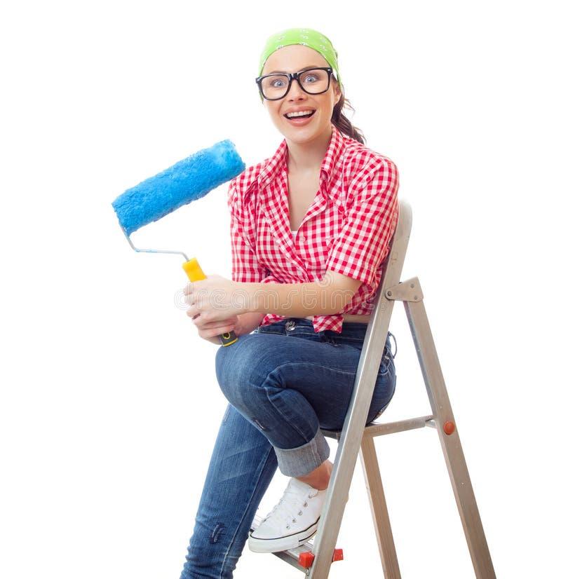 Zdziwiona kobieta z farba rolownika obsiadaniem zdjęcia stock