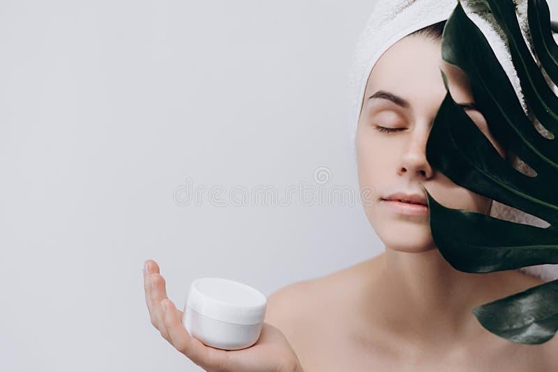 Zdziwiona kobieta z ręcznikiem na jej głowie trzyma wielką zieloną śmietankę dla twarzy i liść obrazy stock