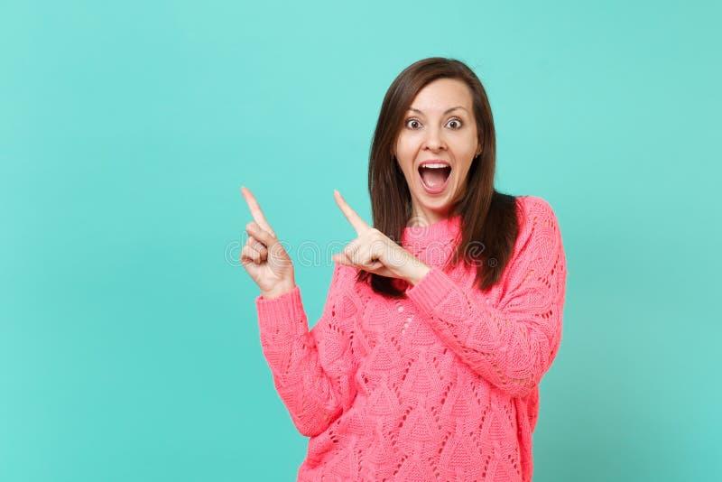 Zdziwiona młoda dziewczyna utrzymuje usta otwartych wskazuje palce wskazujących na boku odizolowywający na błękit ścianie w tryko zdjęcie stock