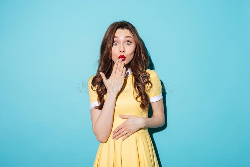 Zdziwiona młoda brunetki kobieta w kolor żółty sukni obrazy stock