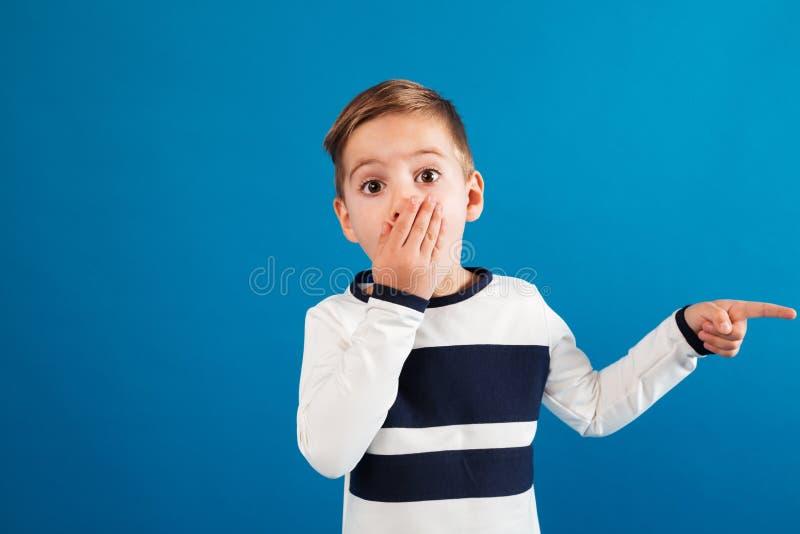 Zdziwiona młoda chłopiec wskazuje daleko od i zakrywa usta w pulowerze zdjęcia royalty free