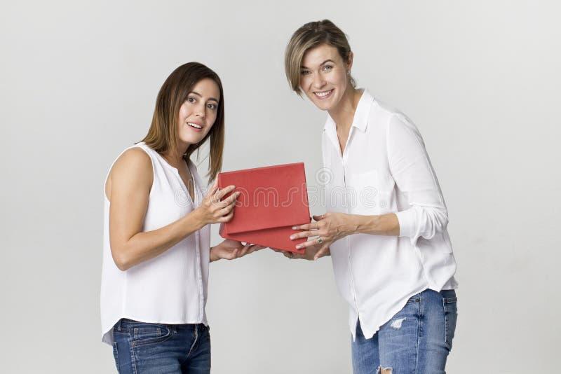 Zdziwiona młoda kobieta dostaje prezent od jej przyjaciela Szczęśliwy i smi fotografia stock