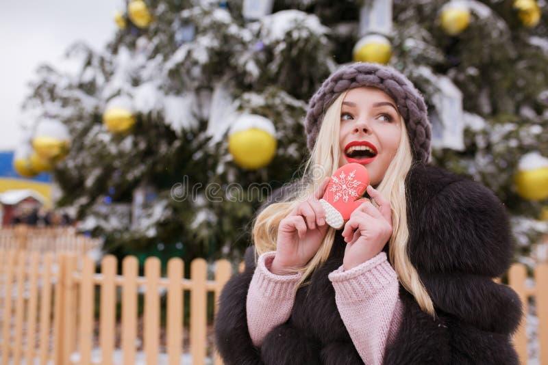 Zdziwiona młoda kobieta ubierał w futerkowym żakiecie i trykotowym kapeluszu, eatin zdjęcie stock