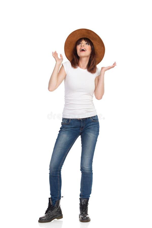 Zdziwiona młoda kobieta W Brown kapeluszu Jest Przyglądająca Up fotografia stock