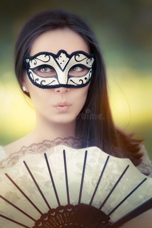 Zdziwiona młoda kobieta z maską i fan obraz stock