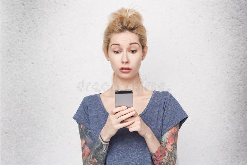 Zdziwiona młoda kobieta z przebijającym nosem i tatuaże używać telefon komórkowego fotografia royalty free