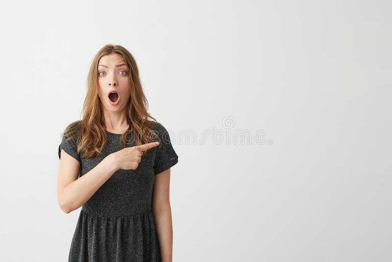 Zdziwiona młoda pozytywna ładna dziewczyna ono uśmiecha się patrzejący kamerę wskazuje palec w stronie nad białym tłem obraz royalty free