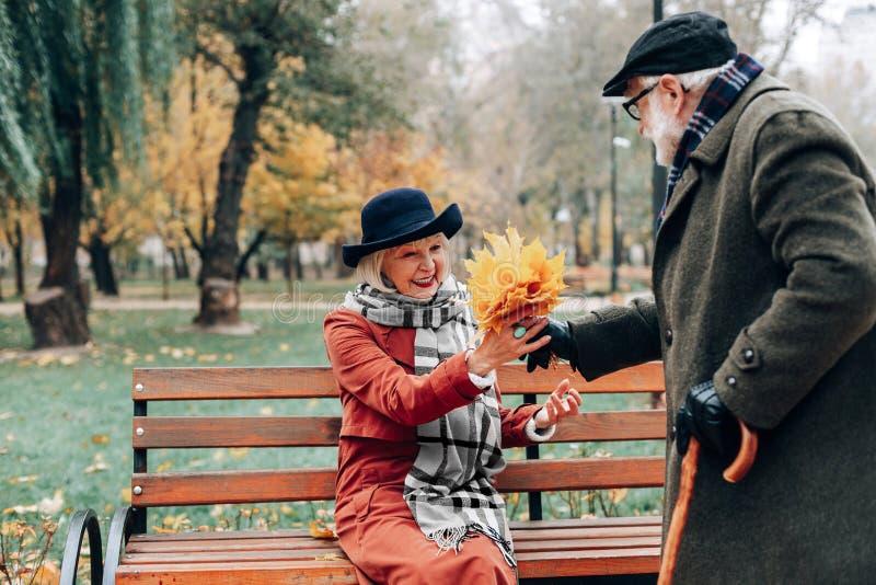 Zdziwiona przechodzić na emeryturę żeńska osoba bierze jesień bukiet zdjęcie royalty free