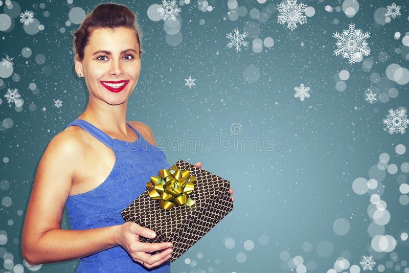 Zdziwiona seksowna dziewczyna trzyma Xmas prezent na bożych narodzeniach przeciw płatkom śniegu na błękitnym tle Portret eleganck fotografia royalty free