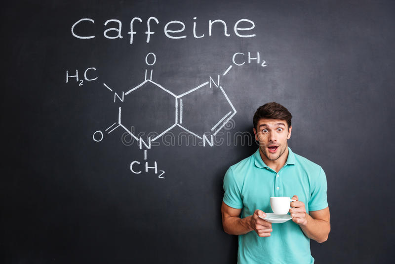 Zdziwiona studencka pije kawa nad patroszoną strukturą kofeiny molekuła obraz stock