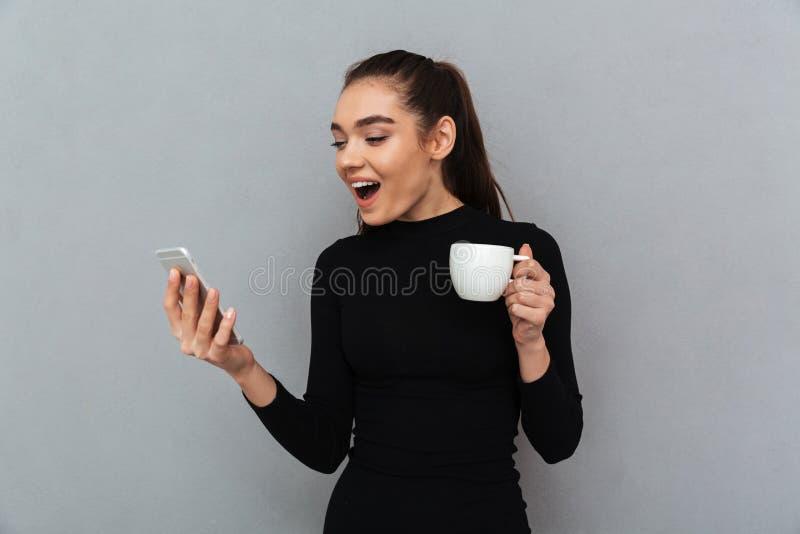 Zdziwiona szczęśliwa brunetki kobieta patrzeje mądrze w czerni ubraniach obraz stock
