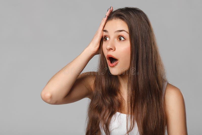 Zdziwiona szczęśliwa kobieta patrzeje z ukosa w podnieceniu, odizolowywającym na szarym tle zdjęcia stock