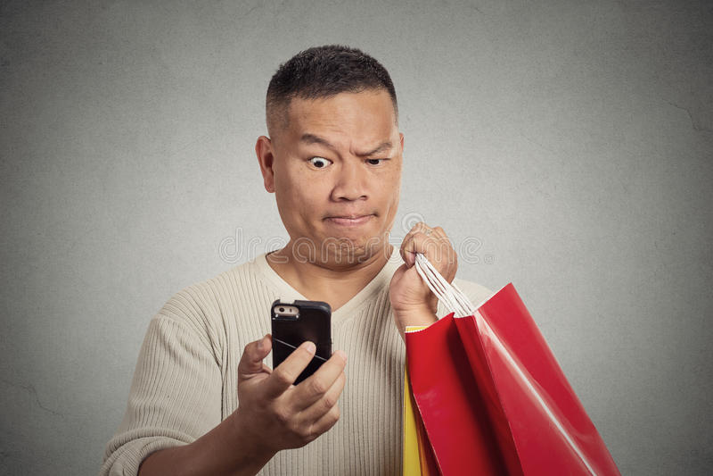 Zdziwionego śmiesznego mężczyzna mienia czerwoni torba na zakupy patrzeje mądrze telefon zdjęcie royalty free