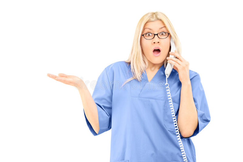 Zdziwionej kobiety doktorski opowiadać na telefonie zdjęcia stock