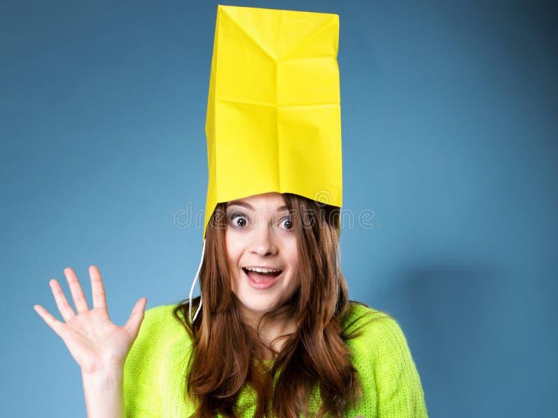 Zdziwiony dziewczyna papieru torba na zakupy na głowie. Sprzedaże. zdjęcia stock