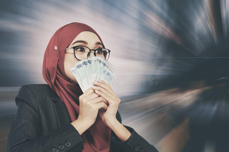 Zdziwionej twarzy mienia wyrażeniowy pieniądze nad abstrakcjonistycznym tłem obrazy stock