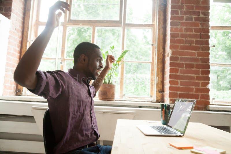 Zdziwiony afroamerykański mężczyzna excited online wygraną patrzeje fotografia stock