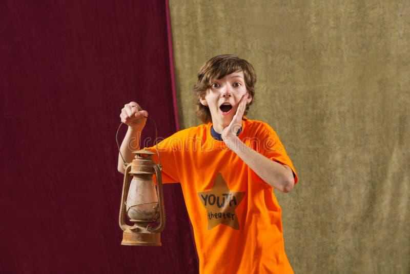 Zdziwiony aktor trzyma lampę obrazy royalty free
