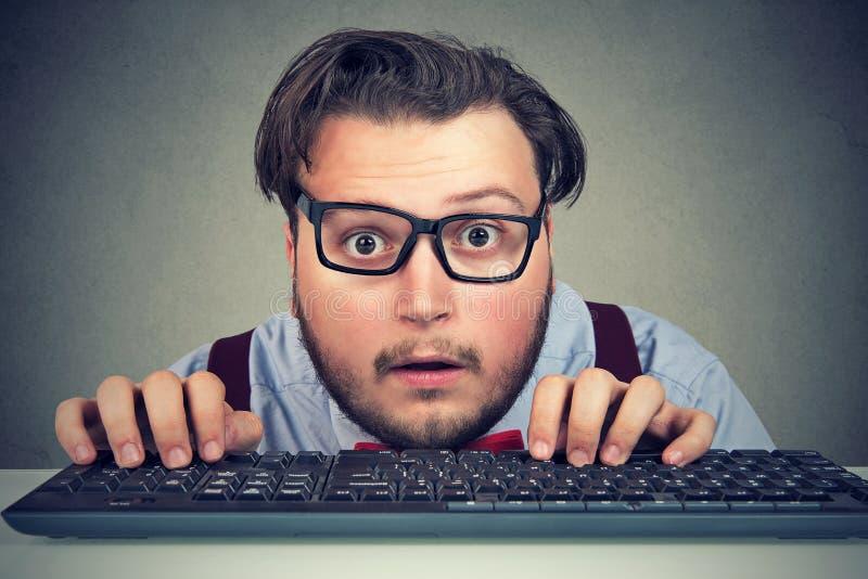Zdziwiony biznesowy mężczyzna pisać na maszynie na kluczowej desce obrazy royalty free