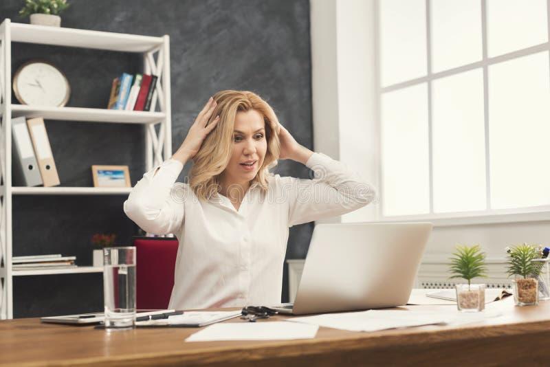 Zdziwiony bizneswoman pracuje na laptopie przy biurem zdjęcia stock