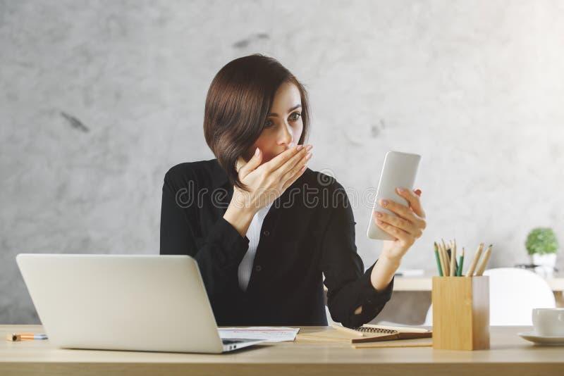 Zdziwiony bizneswoman używa smartphone przy miejscem pracy zdjęcie stock