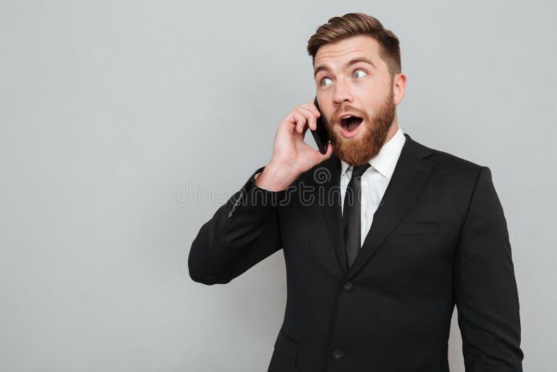 Zdziwiony brodaty mężczyzna opowiada na jego smartphone w kostiumu zdjęcie royalty free