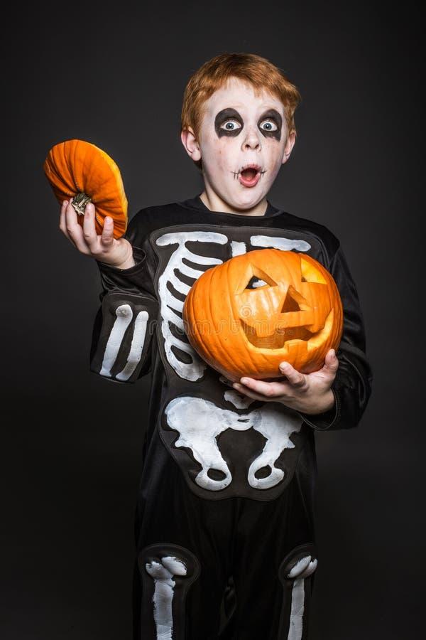 Zdziwiony czerwony włosiany dziecko trzyma pomarańczowej bani w Halloweenowym kostiumu kościec fotografia stock