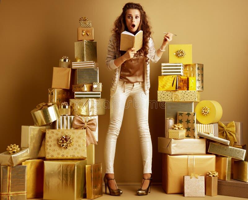 Zdziwiony eleganckiej kobiety mienia notatnik robi li?cie prezenty zdjęcie royalty free