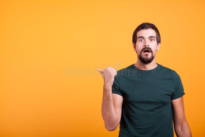 Zdziwiony emocjonalny dorosły mężczyzna wskazuje przy copyspace obraz royalty free