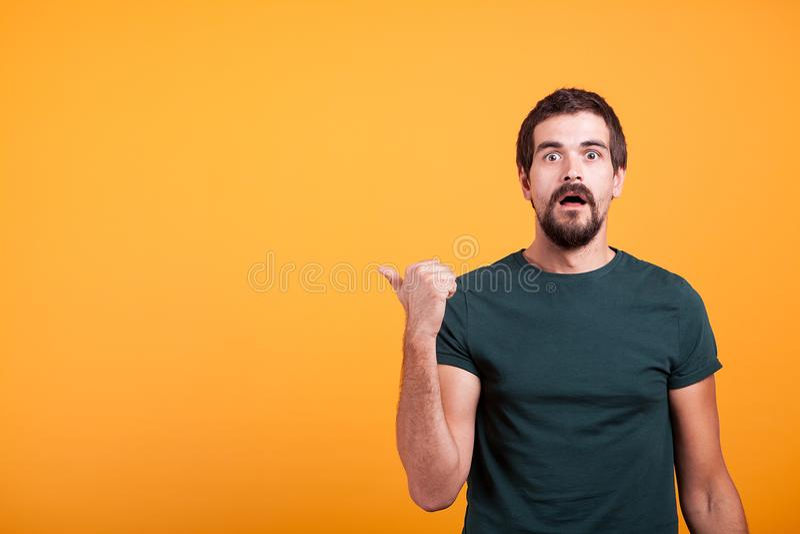 Zdziwiony emocjonalny dorosły mężczyzna wskazuje przy copyspace zdjęcie royalty free