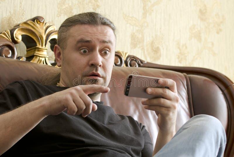 Zdziwiony mężczyzna patrzeje telefon komórkowego fotografia royalty free