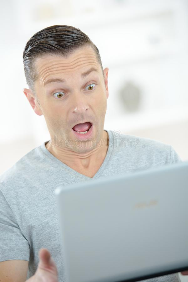 Zdziwiony mężczyzna patrzeje w ekran komputerowego obrazy stock