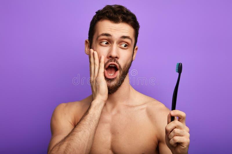 Zdziwiony mężczyzna trzyma toothbrush z palmą na jego policzku obraz stock