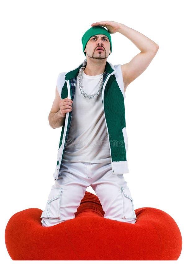 Zdziwiony mężczyzna ubierał jak gnomu obsiadanie na czerwieni zdjęcia stock