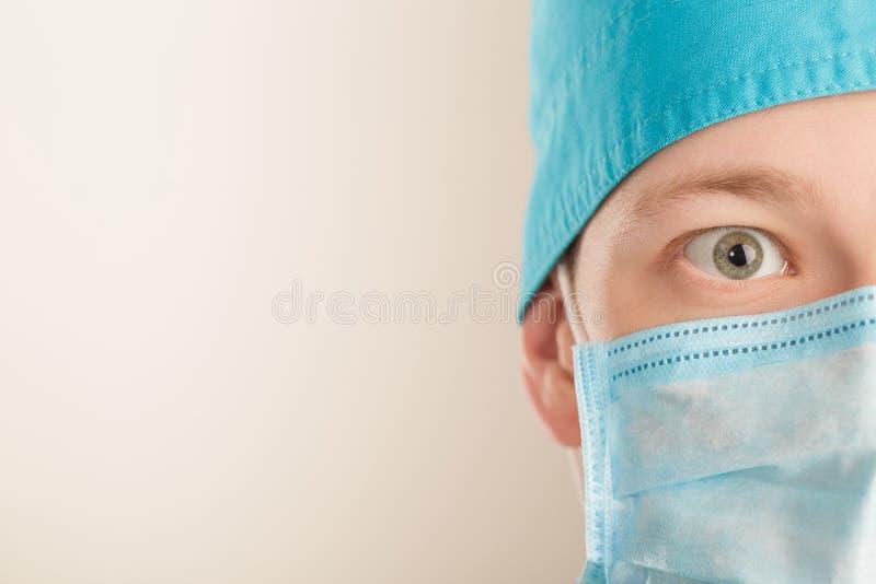 Zdziwiony męski chirurg w maskowej patrzeje kamerze na popielatym tle, zamyka up kosmos kopii obrazy stock