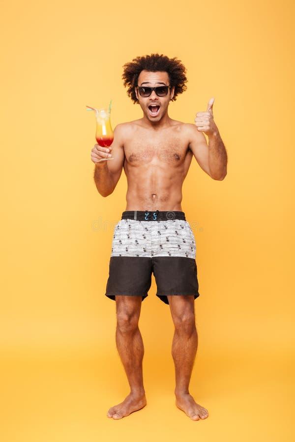 Zdziwiony młody afrykański mężczyzna pije koktajl i pokazuje aprobaty zdjęcia royalty free