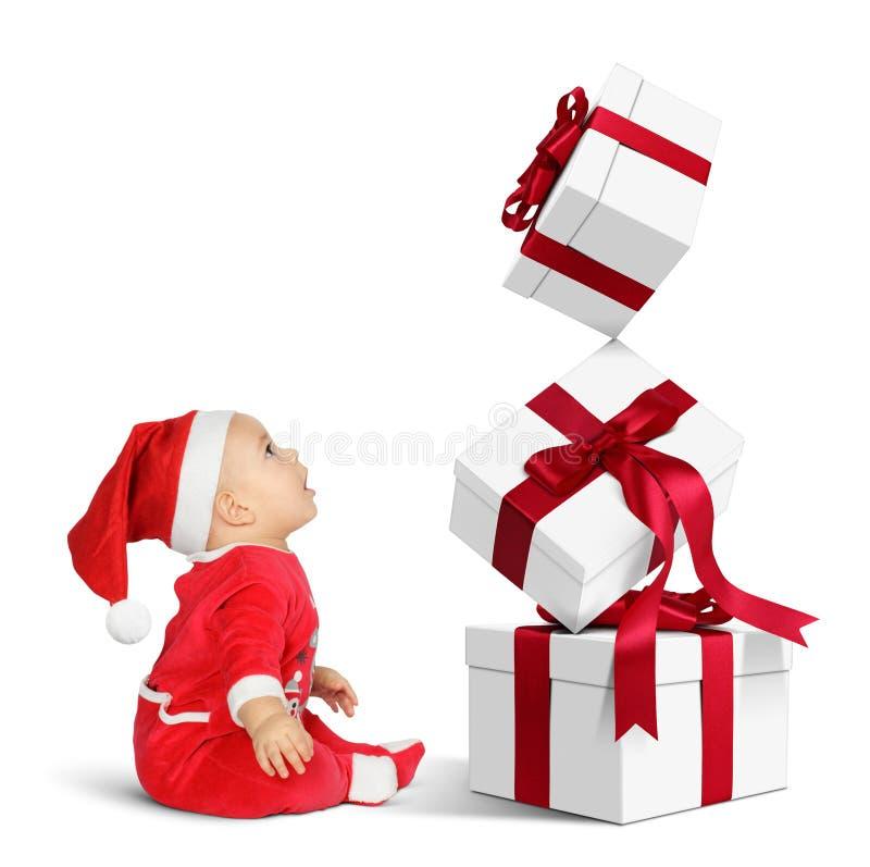 Zdziwiony Mały dziecko Święty Mikołaj z wiele Bożenarodzeniowymi prezentami, sid fotografia royalty free