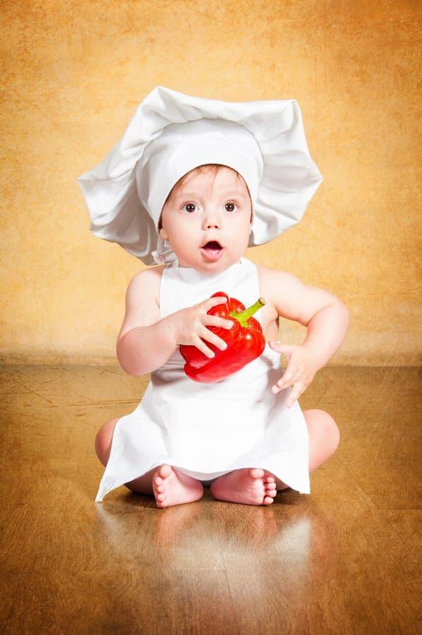 Zdziwiony mały szef kuchni z czerwonym pieprzem w ręce. zdjęcia royalty free