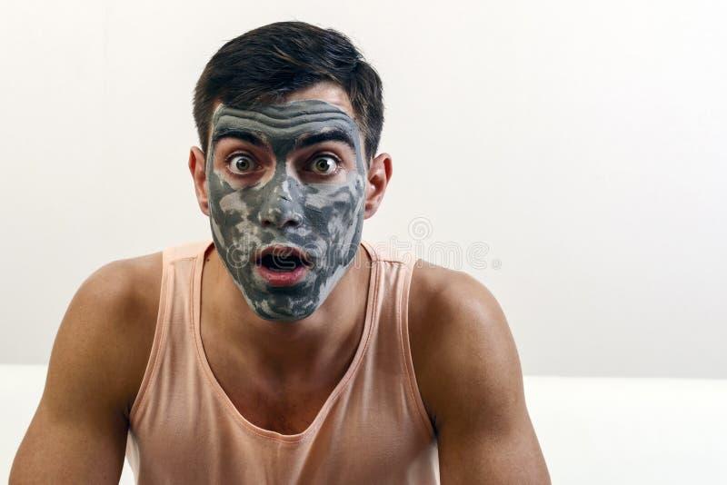 Zdziwiony portret mężczyzna w glinianej masce na jego twarzy stosowanie opieki skóry przejrzystego lakier kosmos kopii obrazy royalty free