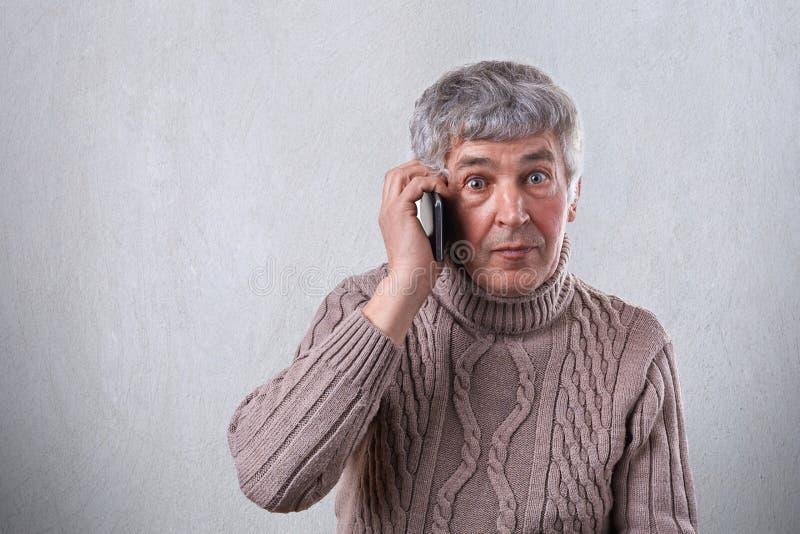 Zdziwiony starsza osoba mężczyzna w pulowerze ma szarych włosianych round ciemnych oczy i zmarszczenia na jego stawiamy czoło kom obrazy royalty free