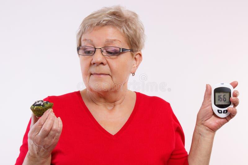 Zdziwiony starszy kobiety mienia glucometer, świeża babeczka i, pojęcie cukrzyce obrazy royalty free
