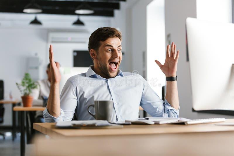 Zdziwiony szczęśliwy męski kierownik raduje się podczas gdy używać komputer obrazy stock