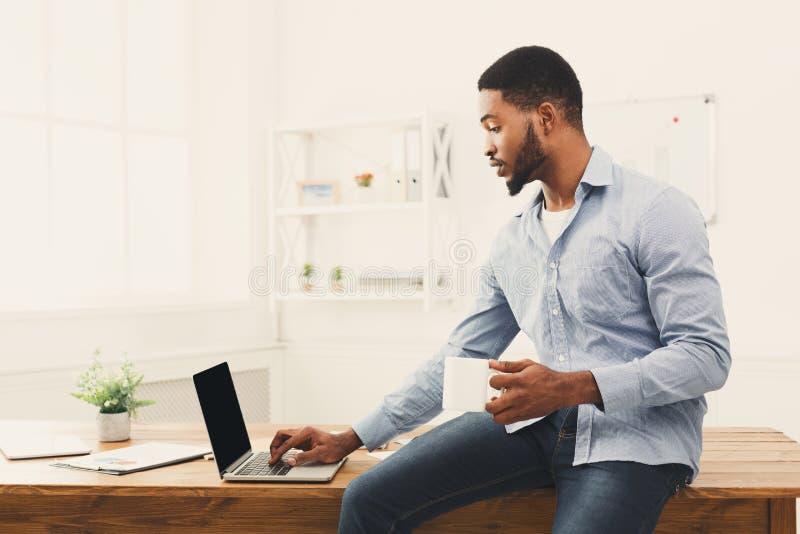 Zdziwiony tylny biznesmen patrzeje laptop obrazy stock